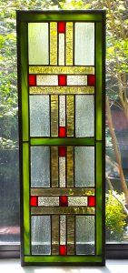 This original design is inspired by Frank Lloyd Wright. Pamela used a very pale seeded green field to offset the linear design.  The red rectangular accents add just the right amount of interest to compliment the golden water glass and olive green opal glass.